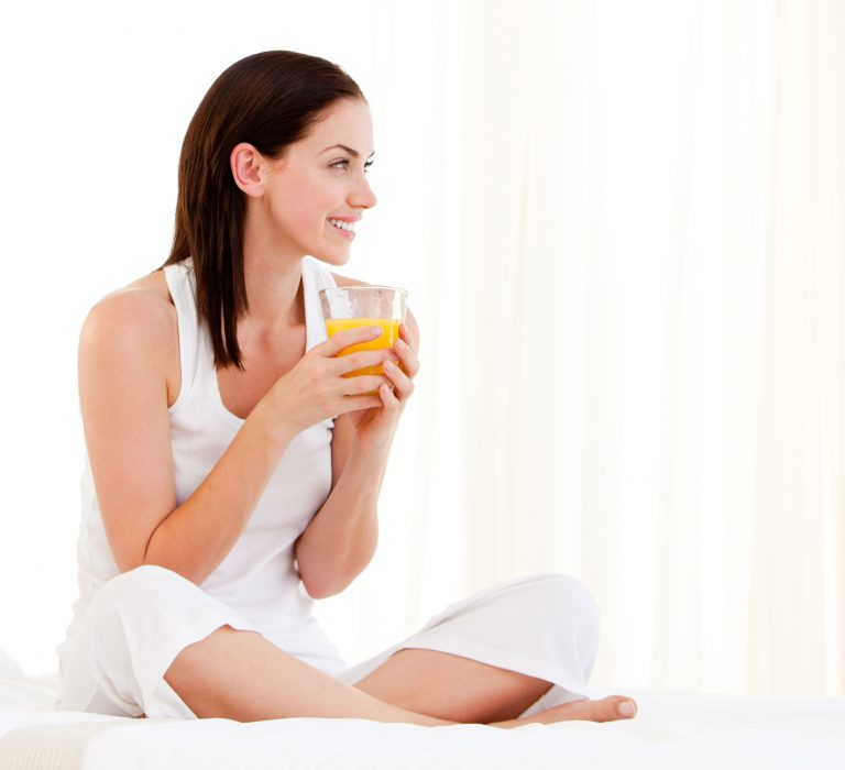 woman enjoying drink during online counseling session