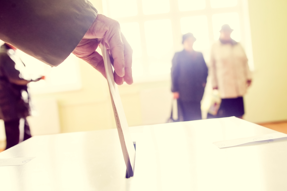 hand dropping ballot into ballot box