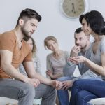 Young woman talking to tense man during anger management class